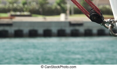Sailboat rope against sea and blurred cars - Detail of...