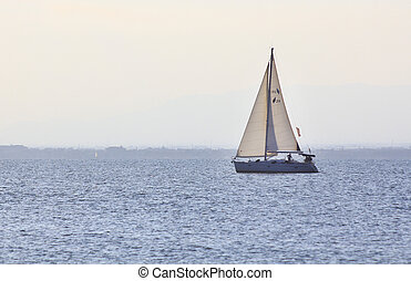 sailboat sailing at sunset
