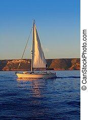 Sailboat sailing golden sunrise in blue ocean