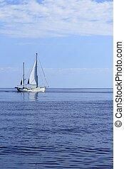 Sailboat sailing on blue sea horizon ocean