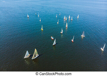 Sailboat shot from above showing the clear blue water of the ocean