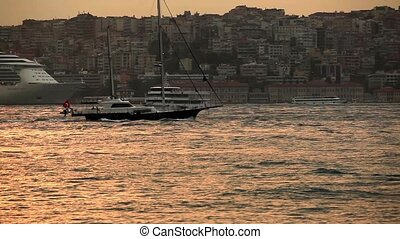 sailboat passing bosphorus at sunset