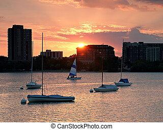 The sun sets on sail boats on Lake Calhoun in Minneapolis, Minnesota.