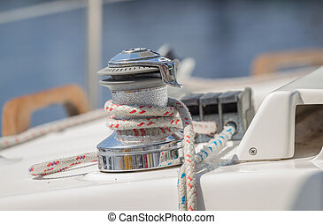 Sailboat winch with rope on yacht deck.