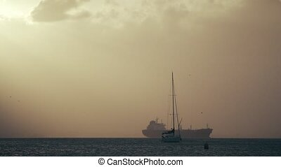 Sailboats against cargo ship at sea sunset - Sailboats...