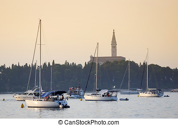 Sailboats anchored in Rovinj harbour at sunset