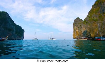 Video UHD - Several private sailboats, bobbing peacefully in the gentle, tropical sea, beneath the towering seacliffs of Phi-Phi Island in southern Thailand.