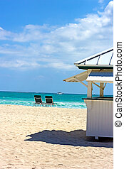 Sailboats at sea and empty chair on the beach. Beach scene, no people.