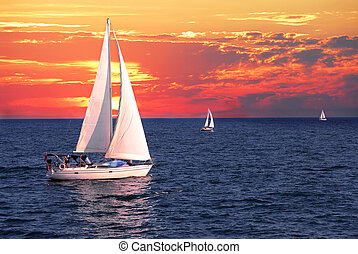 Sailboat sailing on a calm evening with dramatic sunset