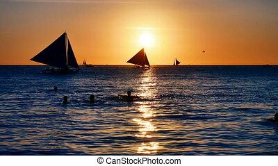 Sailboats cruising at sunset