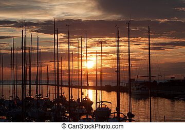 Sailboats in harbor with sunset