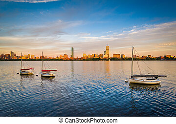 Sailboats in the Charles River at sunset, in Cambridge, Massachusetts.