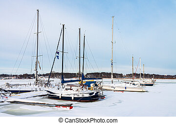 Sailboats in the city port in winter time in Rostock, Germany.
