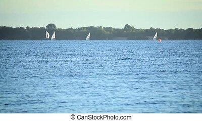 Sailboats sailing on water of sea, lake or river,