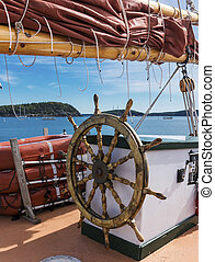 Picture taken from a wooden sailboat while floating around Bar Harbor Maine, with the Porcupine Islands in view under the sail and behind the steering wheel.
