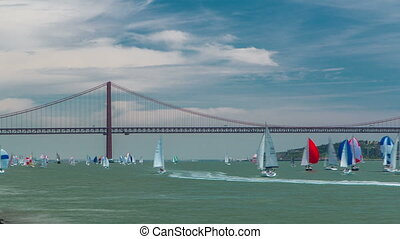 Sailfishes on the Tagus river with 25th of April Suspension Bridge on background timelapse