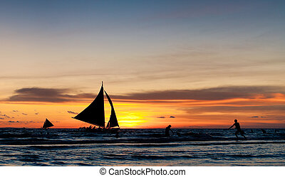 sailing at sunset - tropical beach with sailing boats at...