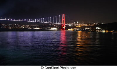 Sailing away from Istanbul's bridge at night