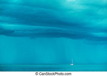 Sailing boat at stormy sea horizon