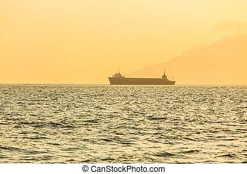 Sailing boat at sunset in ocean