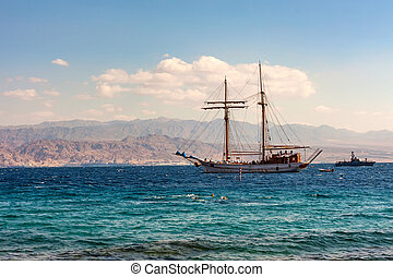 Sailing boat in sea with mountains in background