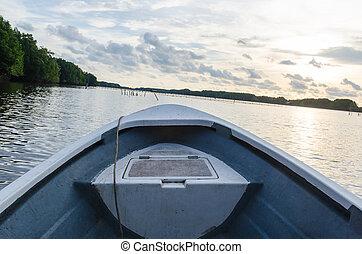 Sailing boat in the lake at sunset
