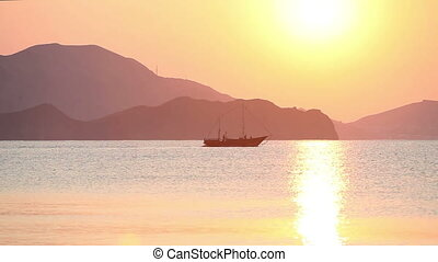 Sailing boat in the sea at sunrise