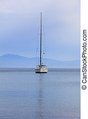 Sailing boat on a blue sea background