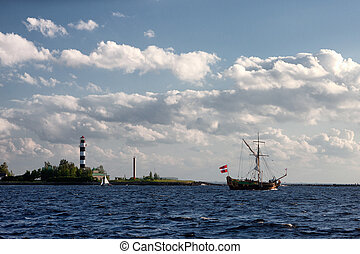 Sailing boat with flag out to sea by the lighthouse