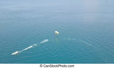 Sailing boat with parasailing in blue sea bay drone view. Aerial view sailing with paragliding in turquoise sea. Beautiful landscape blue lagoon and green island.
