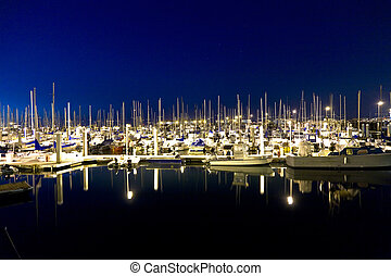 sailing boats in the windless harbor at the pier by night