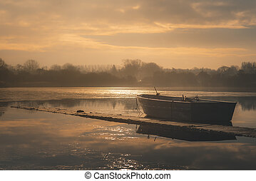 Sailing boats on a lake during a frosty winter sunrise