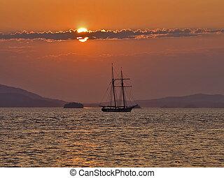 Sailing into the sunse - Double masted sailboat sailing into...