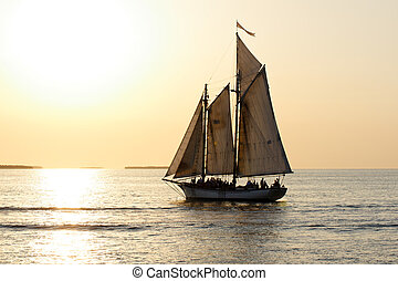 A sailboat full of people is sailing into the sunset before a yellow sky.