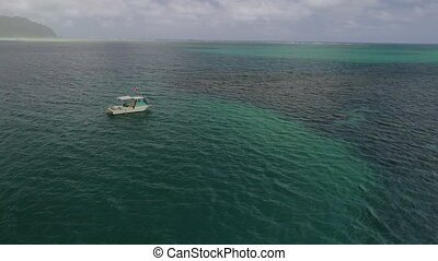 An aerial shot of a boat in the great barrier reef.