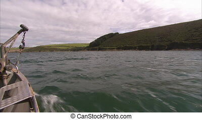 Sailing past a greenfield using a speedboat - A wide shot...
