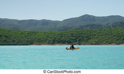 Sailing past a kayaker - A wide shot passing a kayaker on a...