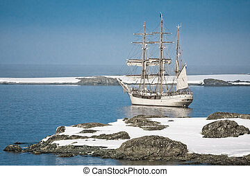 Sailing ship among the icebergs in Antarctica