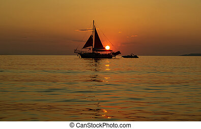 Sailing ship at sea at sunset