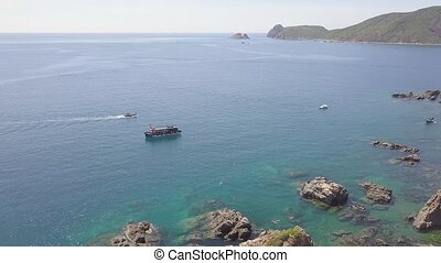 Sailing ship in blue sea water and rocky cliff aerial view. Drone shot boat sailing in sea bay and mountain cliff on shore. Top view blue ocean lagoon.