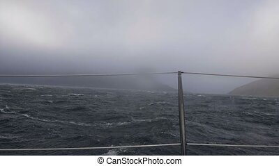 Sailing ship swinging on stormy sea waves view from board. Cruise ship in storm