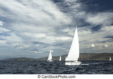 Sailing ship yachts with white sails in a row.