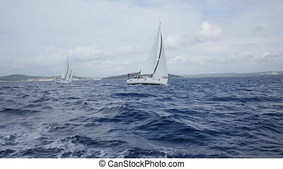 Sailing ship yachts with white sails in open Sea.