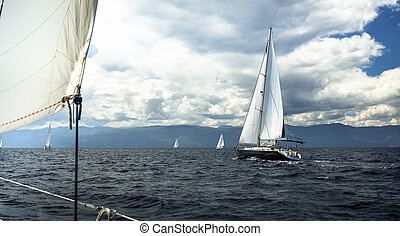 Sailing ship yachts with white sails in stormy weather.