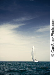 Sailing ship yachts with white sails in the open sea