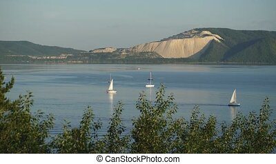 Sailing ships go the river on a background of mountains and forests
