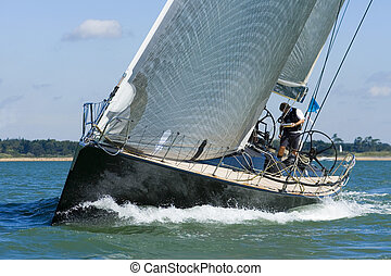 A powerful black racing yacht with wind filled sails powers through coastal waters