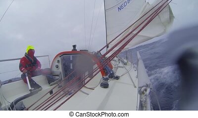 Sailing through rough seas - Single handed sailor steering...