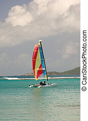 Two people enjoying a beautiful day in a small, colorful sailboat
