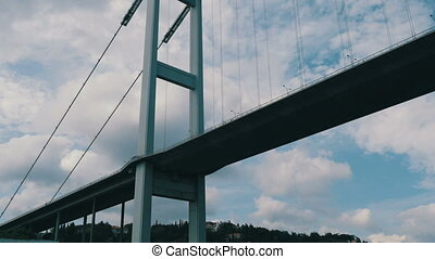 Sailing under large bridge on a tourist boat by sea, ...
